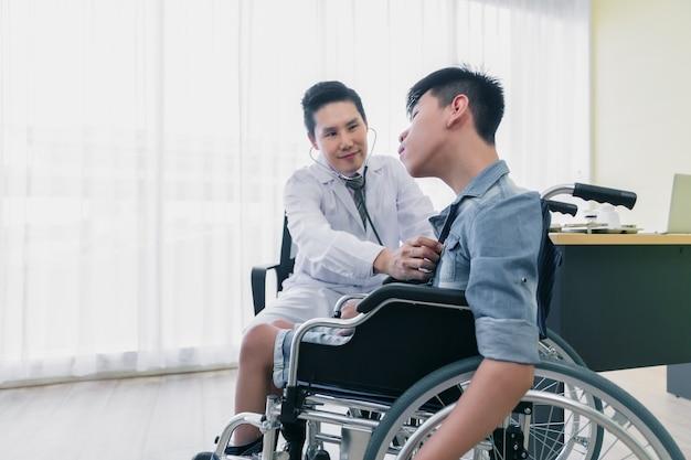 Asiatischer arzt verwendet stethoskop, um rollstuhlpatienten mit behinderung zu untersuchen