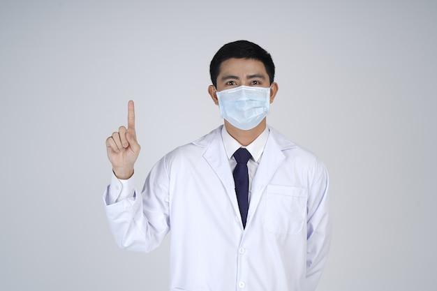 Asiatischer arztmann, der weißen kittel und medizinische maske trägt