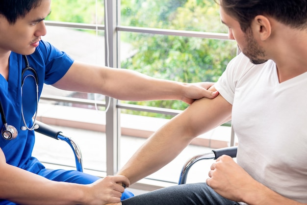 Asiatischer arzttherapeut massiert schmerzenden arm des männlichen athletenpatienten in der klinik für physikalisches therapiekonzept