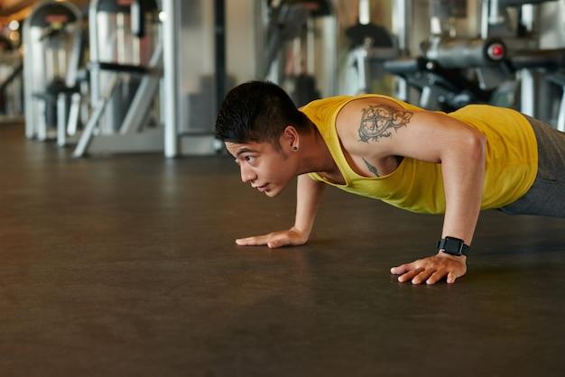 Asiatischer athlet, der liegestütze in einer turnhalle tut