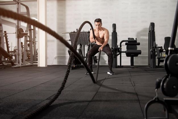Asiatischer athletischer mann mit seil, das übung im fitness-studio tut
