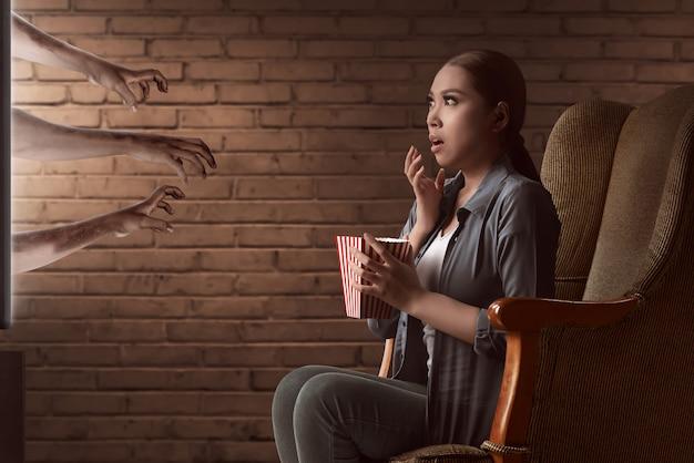 Asiatischer aufpassender horrorfilm der jungen frau und essen das popcorn mit dem sitzen auf sofa