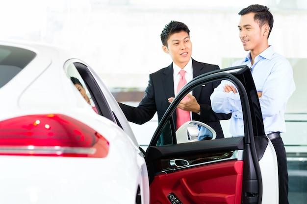 Asiatischer autoverkäufer, der auto an kunden verkauft