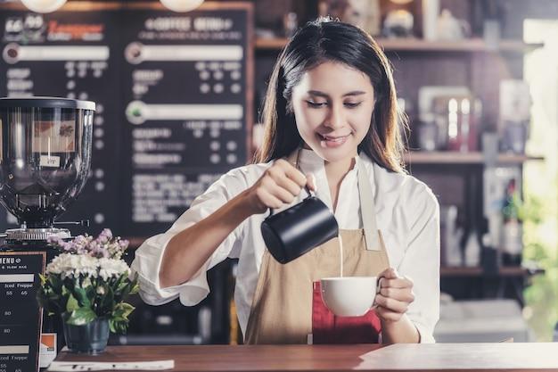 Asiatischer barista, der eine tasse kaffee espresso mit latte oder cappuccino für den kunden zubereitet