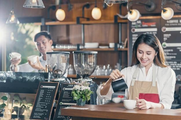 Asiatischer barista, der eine tasse kaffee espresso mit latte oder cappuccino für kundenbestellung zubereitet