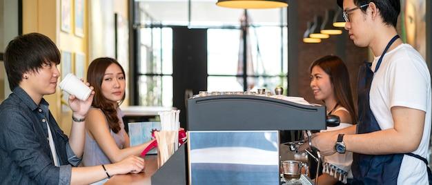 Asiatischer barista, der kaffee mit kaffeemaschine macht und eine tasse cappuccino im coffeeshop serviert