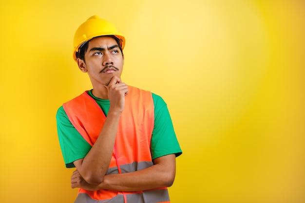 Asiatischer bauarbeiter mit orangefarbener weste und harhut wird auf der suche nach ideen vor gelbem hintergrund gesehen