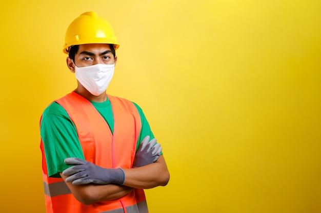 Asiatischer bauarbeitermann mit maske und sicherheitsweste kreuzte seinen arm mit zuversichtsgeste vor gelbem hintergrund