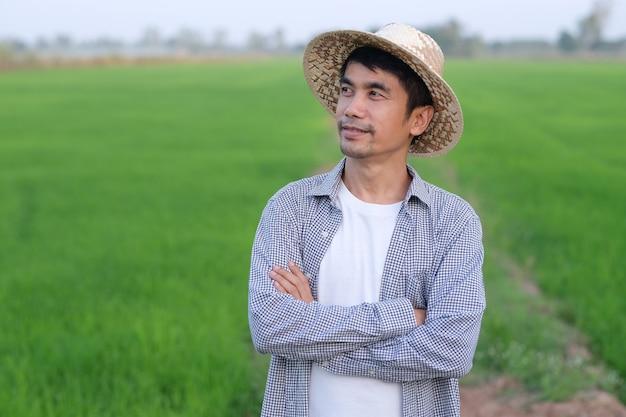 Asiatischer bauernmann, der kreuzarme an der grünen reisfarm steht