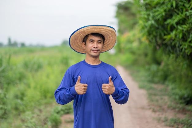 Asiatischer bauernmann lächelt und daumen hoch zwei hände für das gute leben auf einer farm