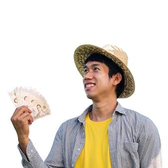 Asiatischer bauernmann lächelt und hält thailändisches banknotengeld