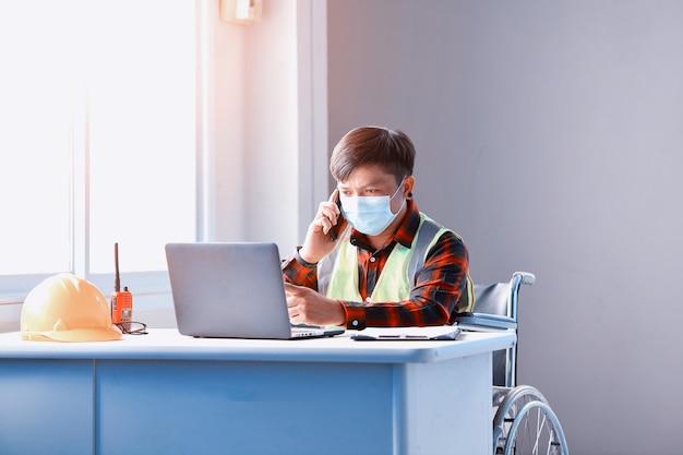 Asiatischer behinderter arbeiter im rollstuhl auf der baustelle der fabrik, bauarbeiter im rollstuhl mit computer