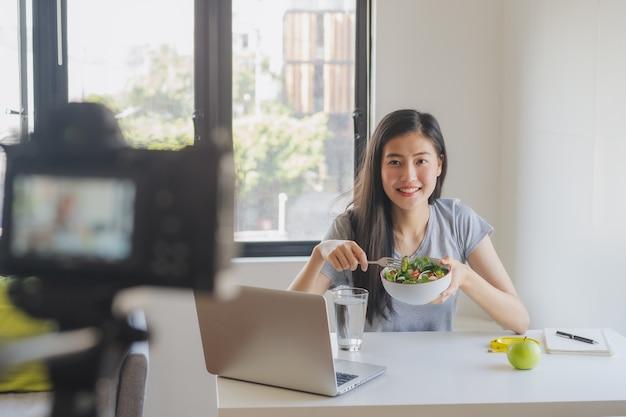Asiatischer blogger, der salat isst und video aufzeichnet