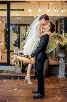 Asiatischer bräutigam hält asiatische braut bis zur höhe und ist im begriff, sich im romantischen gefühl zu küssen.