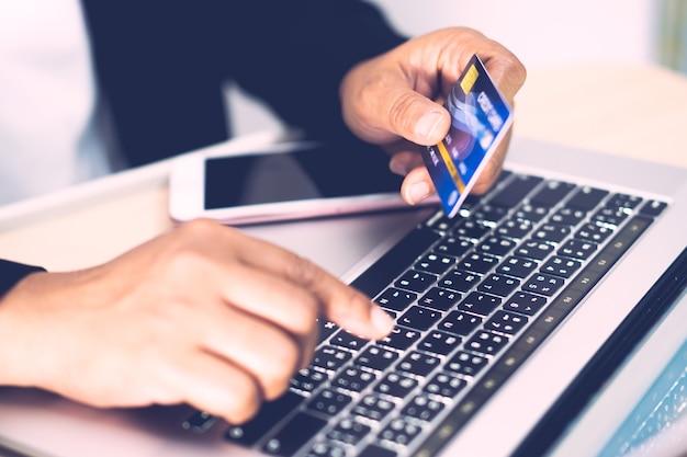 Asiatischer buchhalter arbeitet, berechnet und analysiert berichtsprojektbuchhaltung mit kreditkarte, notebook und handy in modernem büro-, finanz- und geschäftskonzept.