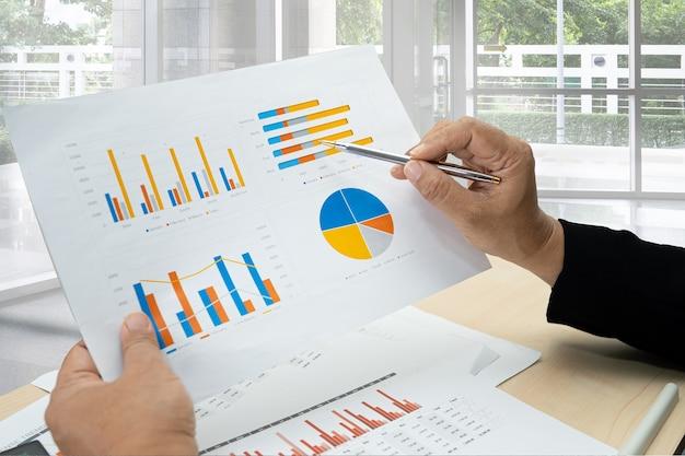 Asiatischer buchhalter arbeitet und analysiert finanzberichte projektbuchhaltung mit diagrammgraphik und taschenrechner im modernen büro-, finanz- und geschäftskonzept.