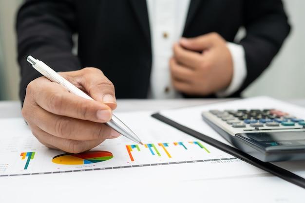 Asiatischer buchhalter arbeitet und analysiert finanzberichte projektbuchhaltung mit diagrammgraphik und taschenrechner
