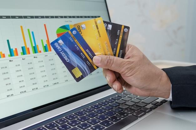 Asiatischer buchhalter, der die projektbuchhaltung mit notebook und kreditkarte im modernen büro-, finanz- und geschäftskonzept arbeitet, berechnet und analysiert.