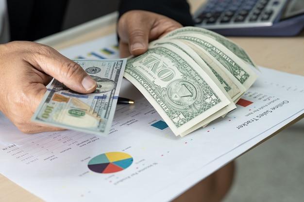 Asiatischer buchhalter, der dollarbanknoten im amt hält.