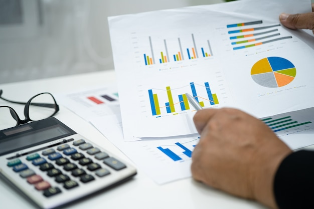 Asiatischer buchhalter, der finanzberichte arbeitet und analysiert, projektbuchhaltung mit diagramm