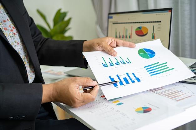 Asiatischer buchhalter, der finanzberichte arbeitet und analysiert, projektbuchhaltung mit diagrammdiagramm