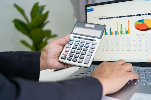 Asiatischer buchhalter, der finanzberichte arbeitet und analysiert, projektbuchhaltung mit grafik