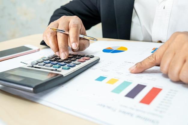 Asiatischer buchhalter, der finanzberichte bearbeitet und analysiert, projektbuchhaltung mit diagrammgrafik und taschenrechner im modernen büro-, finanz- und geschäftskonzept.