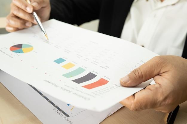 Asiatischer buchhalter, der finanzberichte projektbuchhaltung arbeitet und analysiert