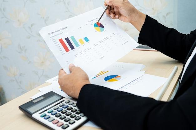 Asiatischer buchhalter, der finanzberichtsprojekt arbeitet und analysiert.
