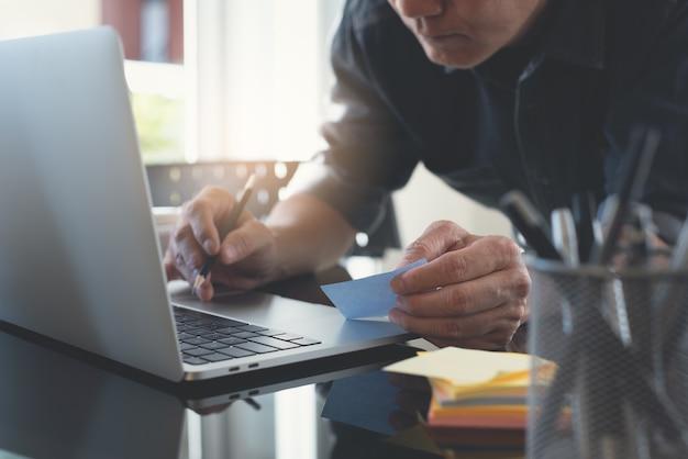 Asiatischer casual business-mann, der zu hause an laptop-computern arbeitet
