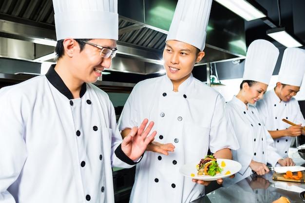 Asiatischer chef beim restaurantküchenkochen
