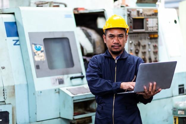 Asiatischer chefingenieur im schutzhelm und arbeiten am computer-laptop über mechanisches stück bei alter fabrikausrüstung.