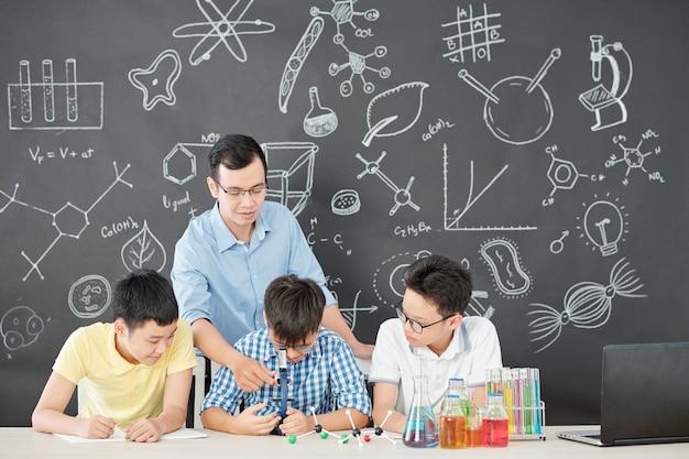 Asiatischer chemielehrer erklärt neugierigen schülern, wie man ein mikroskop benutzt