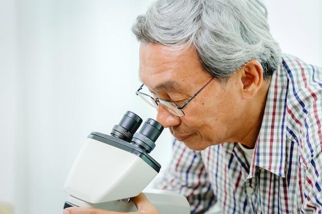 Asiatischer chinesischer arzt, der mikroskop für virusmedizin und forschung im krankenhauslabor betrachtet