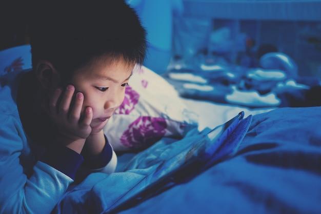 Asiatischer chinesischer junge, der smartphone auf bett, kindgebrauchstelefon spielt und spiel spielt