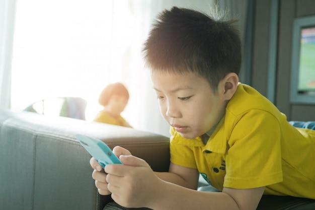 Asiatischer chinesischer junge, der smartphone auf bett spielt, kind benutzt telefon und spielt spiel, süchtig spiel und cartoon,
