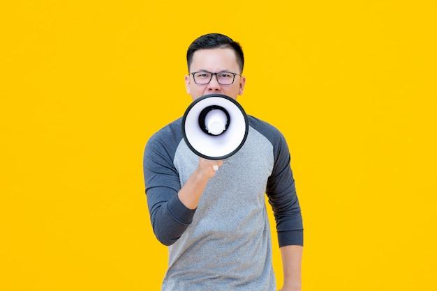 Asiatischer chinesischer mann, der auf megaphon schreit