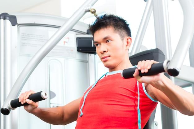 Asiatischer chinesischer mann, der fitness-training oder training in der turnhalle tut, die sport treibt, um muskeln auf einer gewichtsmaschine aufzubauen