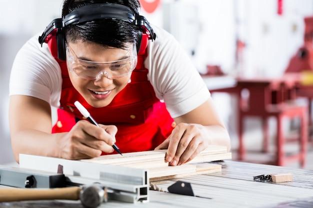 Asiatischer chinesischer zimmermann, der holz mit säge schneidet