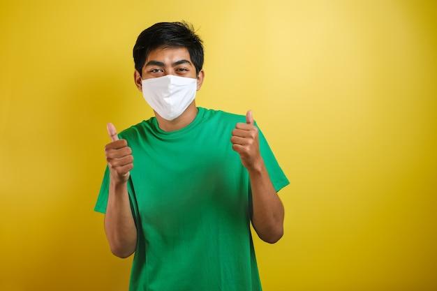 Asiatischer college-studenten-mann daumen hoch und trägt masken, um die ausbreitung des corona-virus vor gelbem hintergrund zu verhindern
