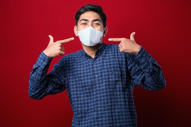 Asiatischer college-studenten-mann daumen hoch und trägt masken, um die ausbreitung des corona-virus vor rotem hintergrund zu verhindern, während er wieder in der schule ist.