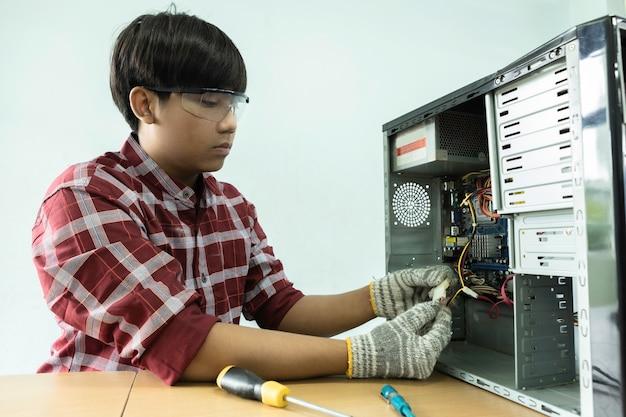 Asiatischer computertechniker, der einen computer repariert