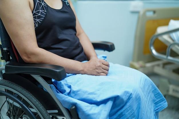 Asiatischer damenfrauenpatient von mittlerem alter auf rollstuhl im krankenhaus.
