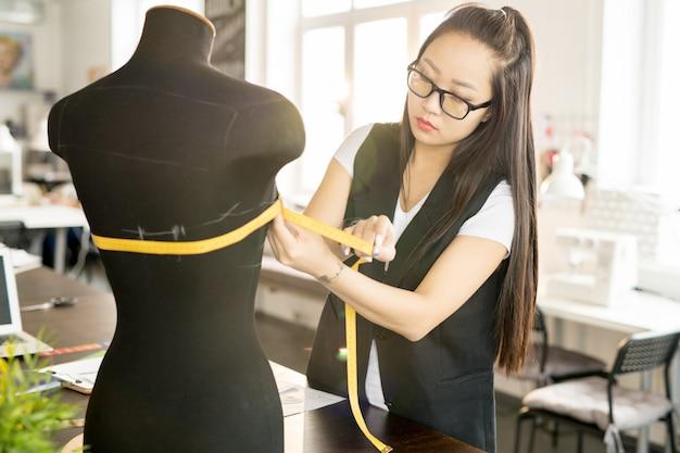 Asiatischer designer, der im sonnenbeschienenen atelier arbeitet