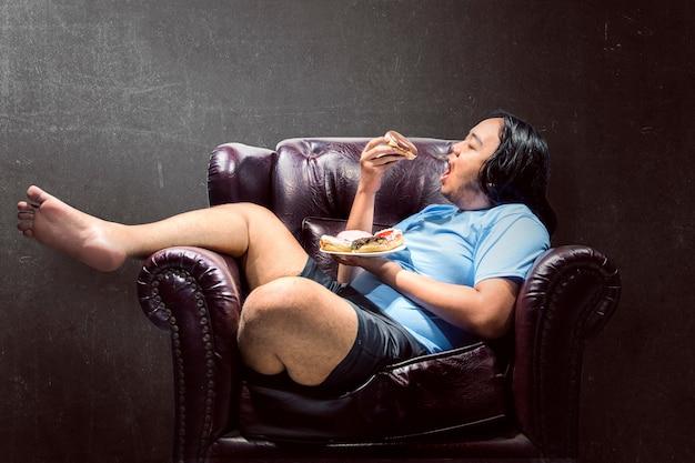 Asiatischer dicker mann, der schaumgummiringe auf der couch eine kleinigkeit isst