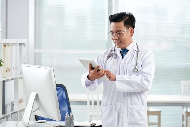 Asiatischer doktor, der medizinische app auf seinem digitalen gerät verwendet