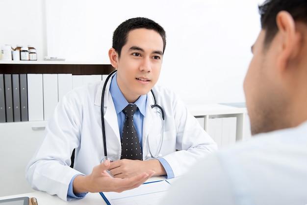 Asiatischer doktor, der mit männlichem patienten spricht