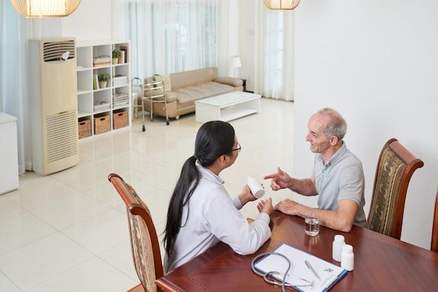Asiatischer doktor, der zu hause mit älterem kaukasischem patienten spricht und medikation bespricht