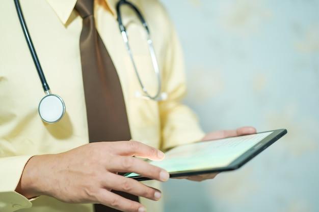 Asiatischer doktor des intelligenten mannes, der digitale tablette hält.