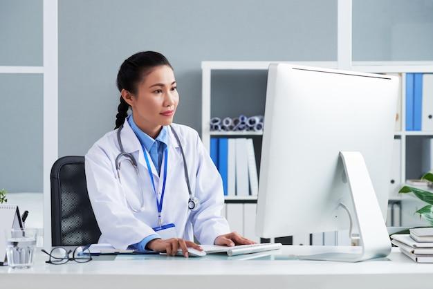 Asiatischer doktor mit stethoskop um den hals, der im büro sitzt und an computer arbeitet